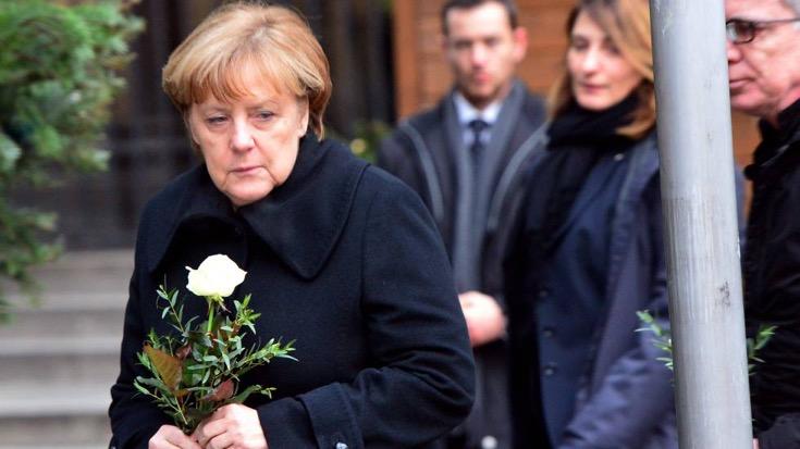Angela Merkel deposita flores en el mercadillo navideño de Berlín donde se produjo el atentado. Maurizio Gambarini/AFP)