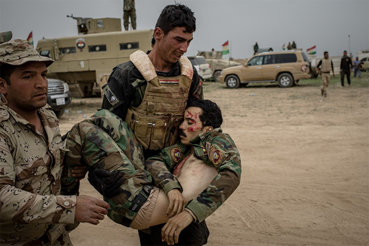 An Iraqi soldier carries the dead body of his brother, who was killed during a battle for the Islamic State-controlled village of Nasr.