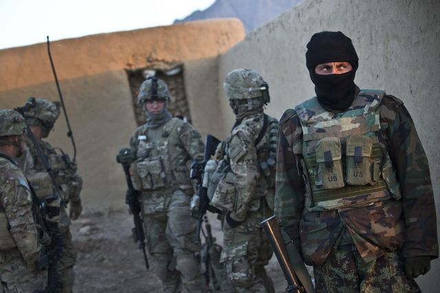 A member of the ANA stands guard outside a compound during a joint patrol with the U.S. Army soldiers in Kandahar province
