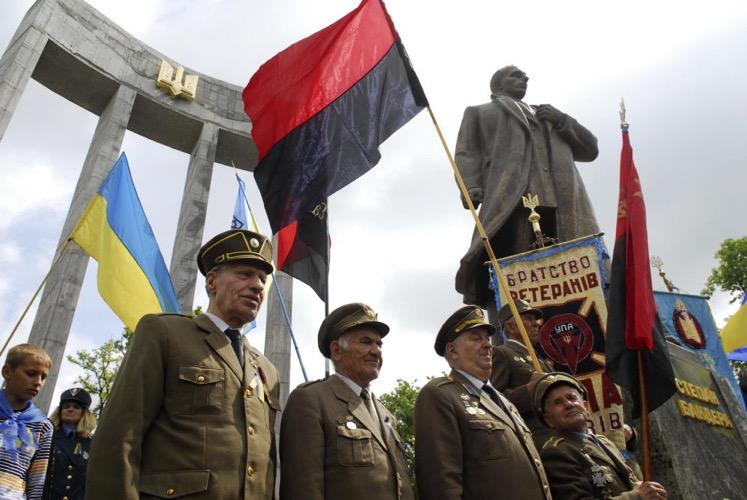 Veteranos del Ejército Insurgente de Ucrania (UPA) junto a la estatua de su fundador, Stepan Bandera, en Lviv, en mayo de 2010 (Reuters)